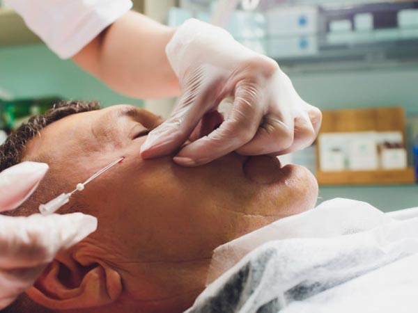 آقايي در عکس وجود دارد که در حال کشيدن صورت خود با استفاده از لفت نخ مي باشد.لباس او سفيد است. پزشک دستکش به دست دارد.