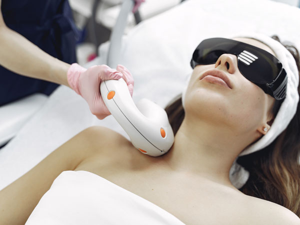 یک خانم روی تخت دراز کشیده است و چشمان خود را بسته است. خانم در حال جوانسازی پوست خود با استفاده از لیزر می باشد. یک حوله بر تن بیمار می باشد. پزشک دارد با استفاده از لیزر پوست بیمار را جوان می کند.