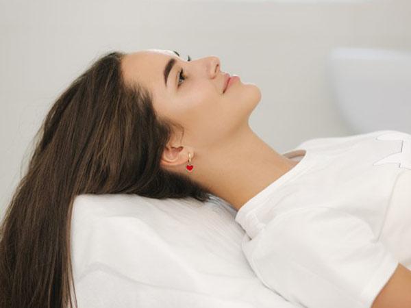 يک خانم جوان روي تخت دراز کشيده است و درحال لبخند زدن می باشد. موهاي بلندي دارد و تي شرت سفيدي به تن کرده است. موهاي او قهوه اي تيره مي باشد