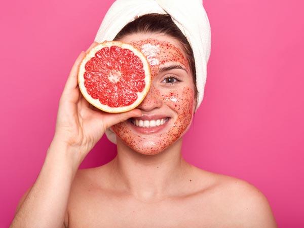 خانم به صورت خود کرم طبیعی زده است. خانم دارد لبخند می زند. به سر خود یک حوله پیچیده است. یک تکه پرتقال در دست دارد.