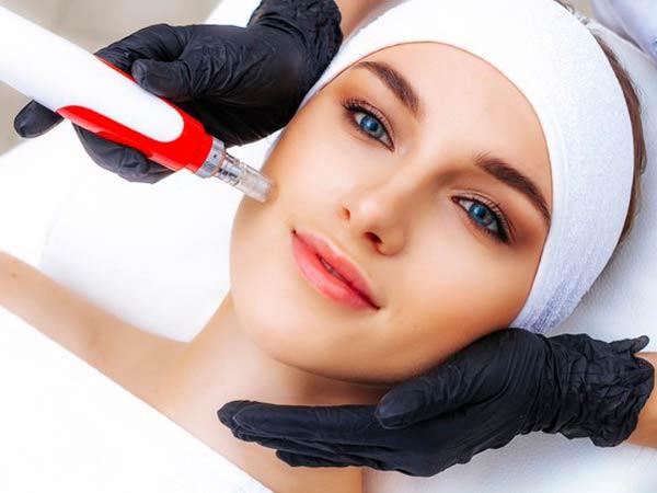 خانمي با چشم هاي رنگي بر روي تخت دراز کشيده است. خانم صورتي صاف و روشن دارد. پزشک با دستکش هايي مشکي درحال انجام مزونيدلينگ بر روي صورت خانم مي باشد.خانم هدبند سفيد به سر دارد.