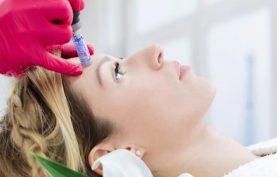 یک خانم در حال انجام میکرونیدلینگ بر روی پوست صورت در ناحیه پیشانی است و پزشکی با دستکش قرمز رنگ و دستگاه درماپن در حال جوانسازی است موی خانم طلایی بوده و ریلکس روی تخت خوابیده است