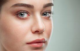 خانمي با صورتي زيبا و صاف درحال نگاه کردن به دوربين مي باشد.خانم چشم هاي رنگي دارد. ابروهاي کشيده و زيبا دارد.