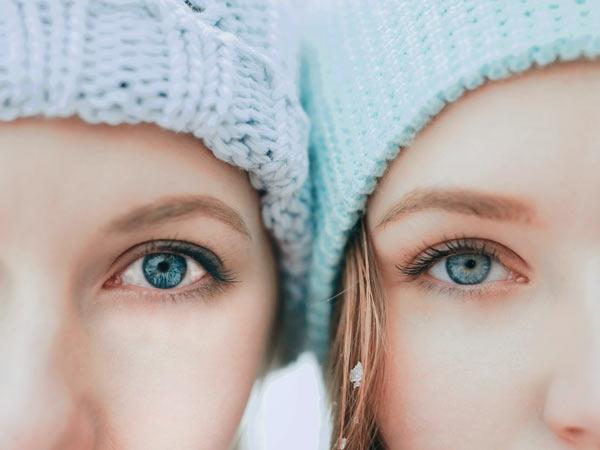 دو خانم کنار یکدیگر ایستاده اند. هر دو چشما هایی رنگی دارند و کلاه بافتنی به سر کرده اند.