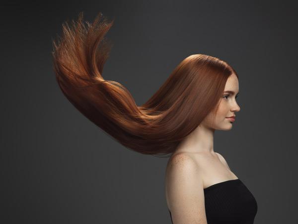 خانم داخل عکس مو زیبایی دارد. رنگ موخانم عسلی می باشد. لباس خانم مشکی است. پی زمینه عکس خاکستری می باشد.