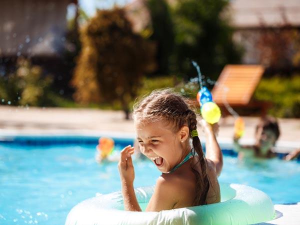 دختر بچه اي در استخر درحال شنا مي باشد. دختر بچه درحال خنديدن است. او درون يک تيوب شنا قرار دارد.موهاي خود را بار کش مو بسته است.