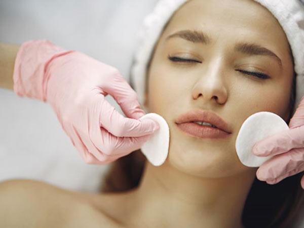 خانمی که چشم هایش را بسته و خوابیده است. صورت خانم را دارند پس از انجام روش های جوانسازی با پد بهداشتی تمیز می کنند. دکتر دستکش های صورتی دارد. خانم در حال جوانسازی پوست می باشد.
