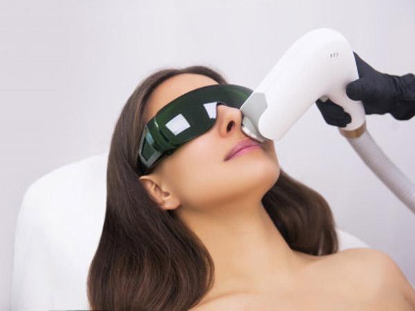 خانمي روي تخت دراز کشيده است. عينک مخصوصي به چشم زده و درحال کربن دي اکسيد درماني مي باشد. پزشک با استفاده ازدستگاه مخصوص کربن دي اکسيد درماني درحال جوانسازی و ترميم پوست صوزرت خانم مي باشد.