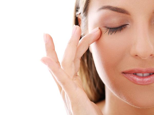 پوست صورت خانم صاف و ضفاف است. چشم های خانم بسته است. خانم دارد با انگشتانش پوست صورت خود را نوازش می کند.