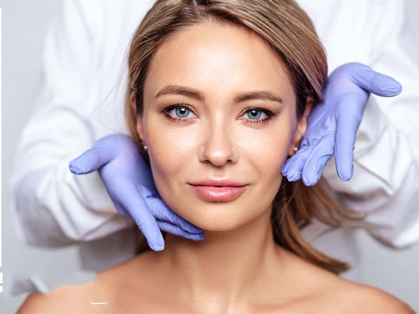 یک خانم داخل نصویر می باشد که پوستی صاف داشته و دستکش بنفش اطراف صورت او وجود دارد. خانم به کمک روش های جوانسازی پوست خود را زیبا کرده است.