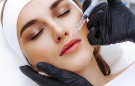 یک خانم در حال تزریق ژل به ناحیه حاشیه لب هایش توسط پزشک می باشد . زمینه تصویر سفید ، دستکش پزشک مشکی و تصویر بیمار بصورت بسته می باشد