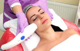 خانمي در تصوير روي تخت خوابيده و پزشک با استفاده از روش ار اف در حال جوانسازي پوست صورت او مي باشد. خانم حوله اي سفيد به تن کرده و پزشک لباس و دستکشي صورتي پوشيده است.
