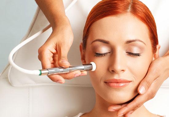 تصویر یک خانم خوابیده بر روی تخت مطب یک پزشک در حال انجام میکرودرم صورت برای شادابی پوست خود است شیلنگ وکیوم سفید و زمینه تصویر هم سفید است . موهای خانم حنایی می باشد
