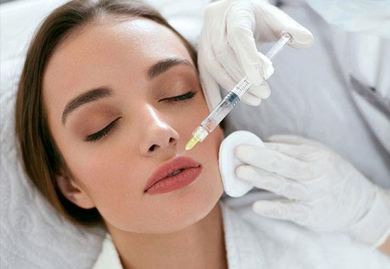 تصویر صورت یک خانم در حالت تزریق لوتاکس لب ، خوابیده بر روی تخت مطب . سرنگ پزشک کاملا نمایان است. این تصویر با مقاله بوتاکس لب در ارتباط می باشد