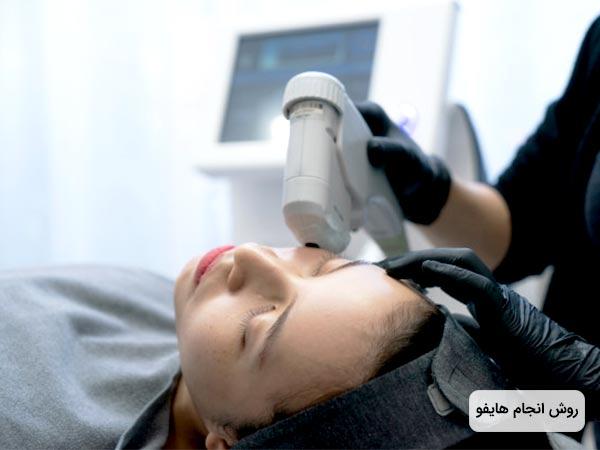 خانمي روي تخت با چشمان بسته دراز کشيده و پزشک در حال جوانسازي پوست صورت او با استفاده از هايفو تراپي است. پزشک دستکش مشکي به دست دارد و بيمار يک هدبند مشکي به سر کرده است.