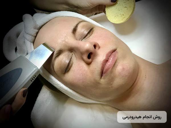 يک خانم روي تخت دراز کشيده است و چشمان خود را بسته است. پزشک درحال زيباسازي و آبرساني به پوست صورت او با استفاده از روش هيدرودرم ابريژن مي باشد.