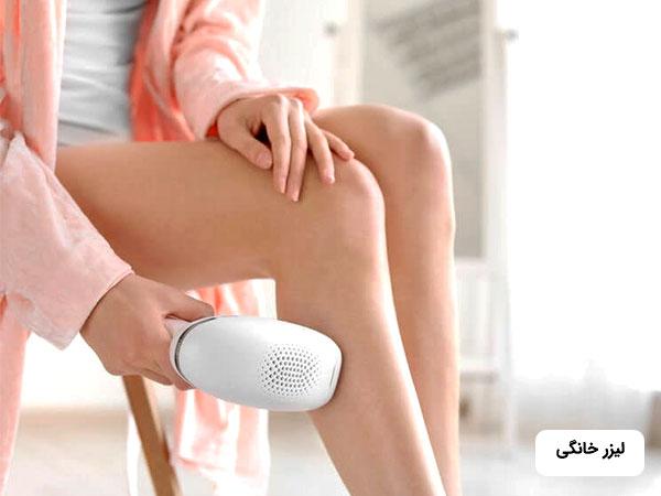 خانمي که حوله صورتي به تن کرده است در حال ليزر موهاي زائد پاي خود بوسيله دستگاه ليزر خانگي مي باشد.