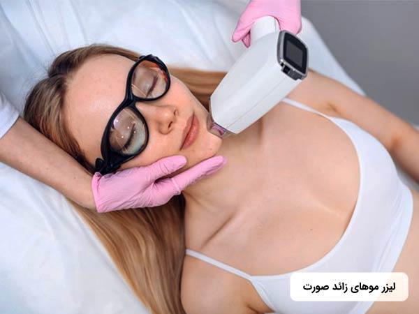 خانمي روي تخت دراز کشيده و چشمان خود را بسته است. پزشک در حال رفع موهاي ناخواسته چانه او با استفاده از روش ليزر موهاي زائد مي باشد.