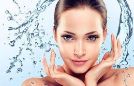 خانم جواني که پوست صافو شادابي دارد، دست هاي خود را زير چانه قرار داده و قطره هاي آب در حال برخورد به صورت او هستند