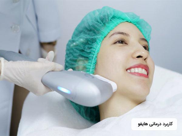 خانم جواني کلاه مخصوصي به سر کرده است و روي تخت دراز کشيده است. او در حال لبخند زدن مي باشد و پزشک در حال زيباسازي و سفت کردن پوست صورت خانم است.